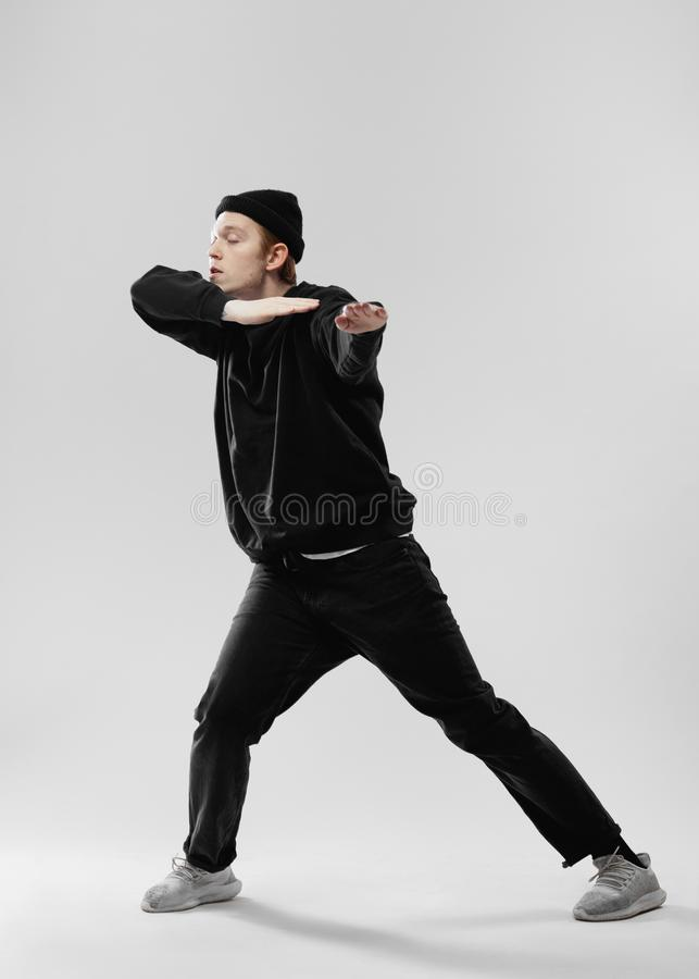 Dancer dressed in black jeans, sweatshirt, hat and gray sneakers is dancing making movements with his hands in the. Studio on the white background royalty free stock photography