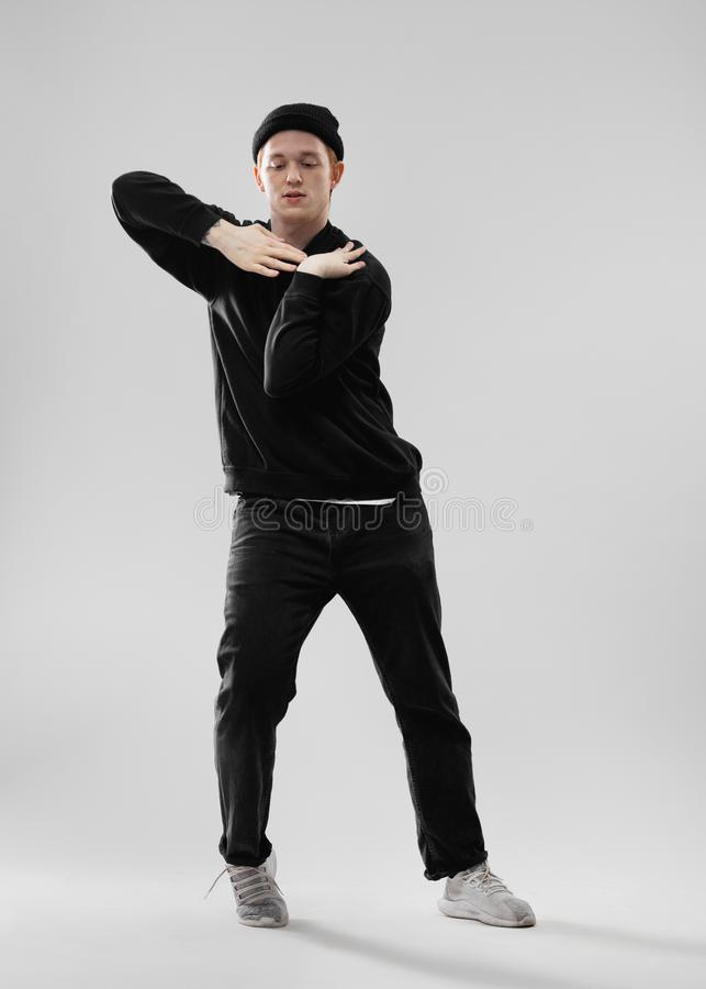 Dancer dressed in black jeans, sweatshirt, hat and gray sneakers is dancing making movements with his hands in the. Studio on the white background stock photography