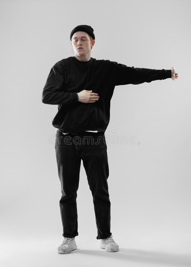 Dancer dressed in black jeans, sweatshirt, hat and gray sneakers is dancing making movements with his hands in the. Studio on the white background stock image