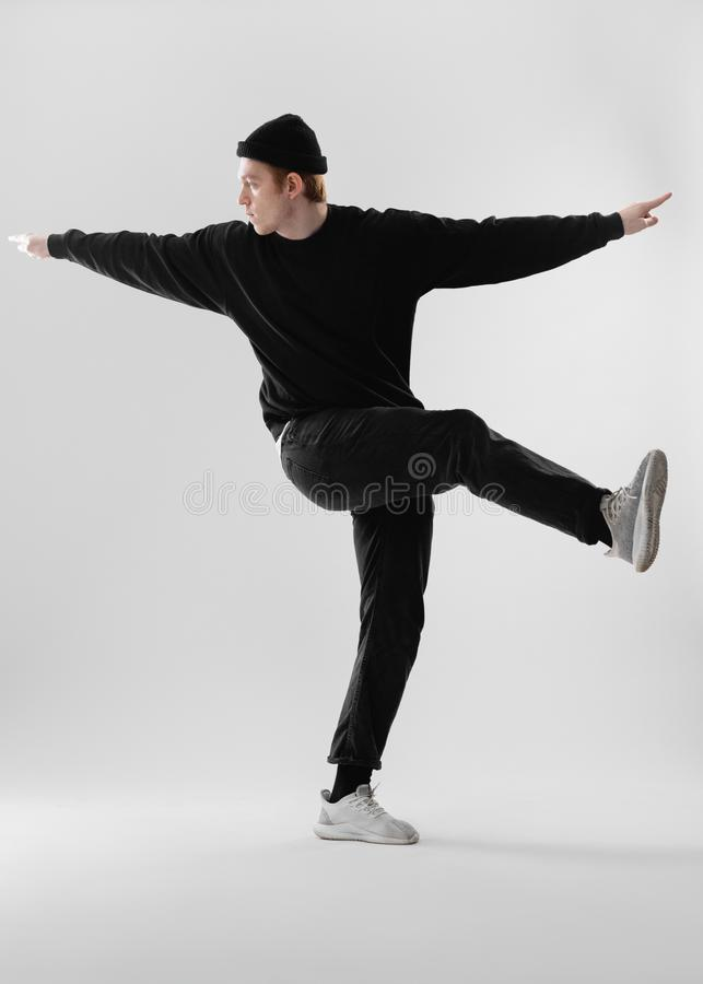 Dancer dressed in black jeans, sweatshirt, hat and gray sneakers is dancing making movements with his legs in the studio. On the white background stock images