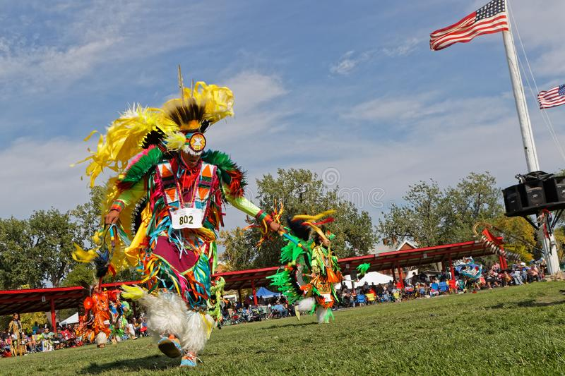 Dancer and flag the 49th annual United Tribes Pow Wow. BISMARK, NORTH DAKOTA, September 8, 2018 : A dancer of the 49th annual United Tribes Pow Wow, one large royalty free stock image