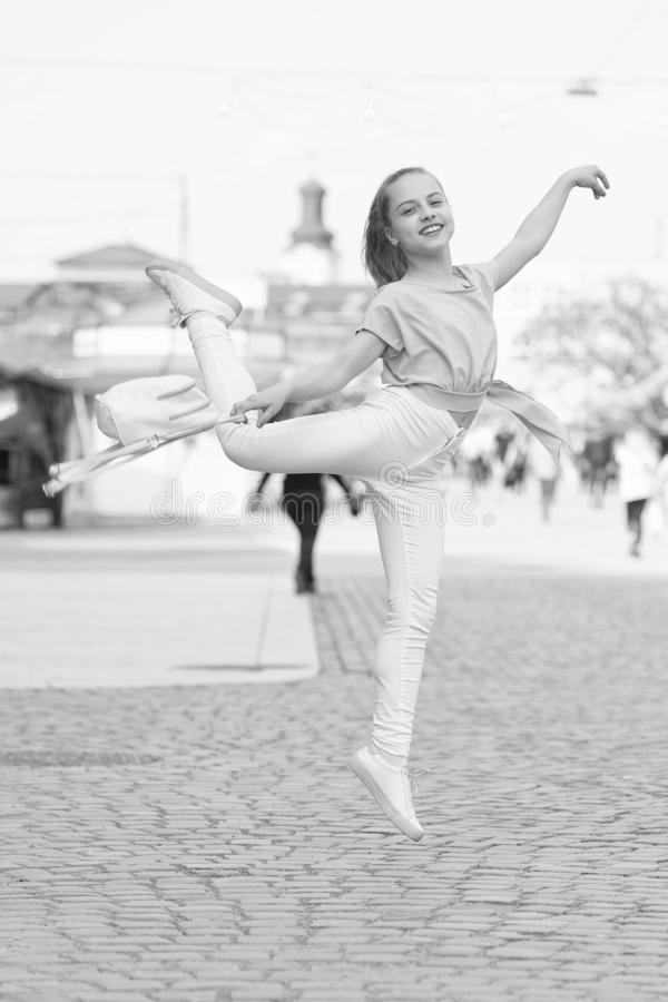 The dancer is at her best. Adorable street dancer. Little female dancer performing ballet leap on street. Small cute royalty free stock photo