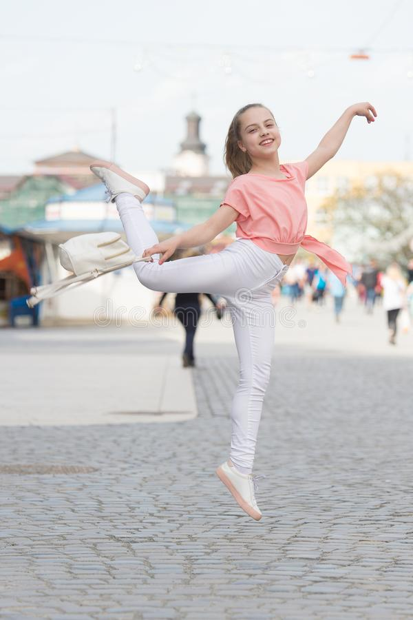 The dancer is at her best. Adorable street dancer. Little female dancer performing ballet leap on street. Small cute stock photos