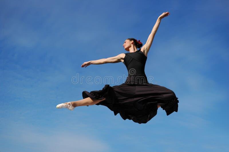 Dancer jumping against blue sk. Y wearing black royalty free stock image