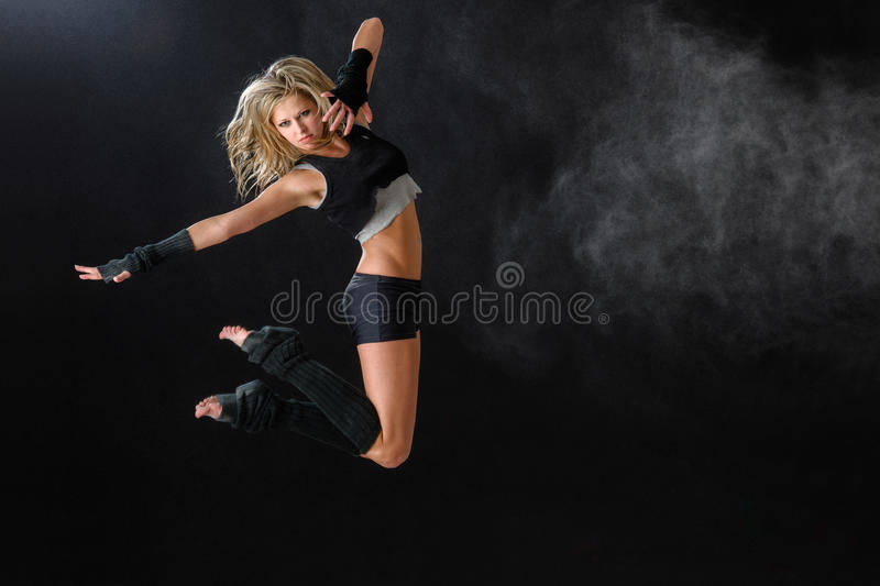 Dancer jumping while performing her dance routine royalty free stock photography