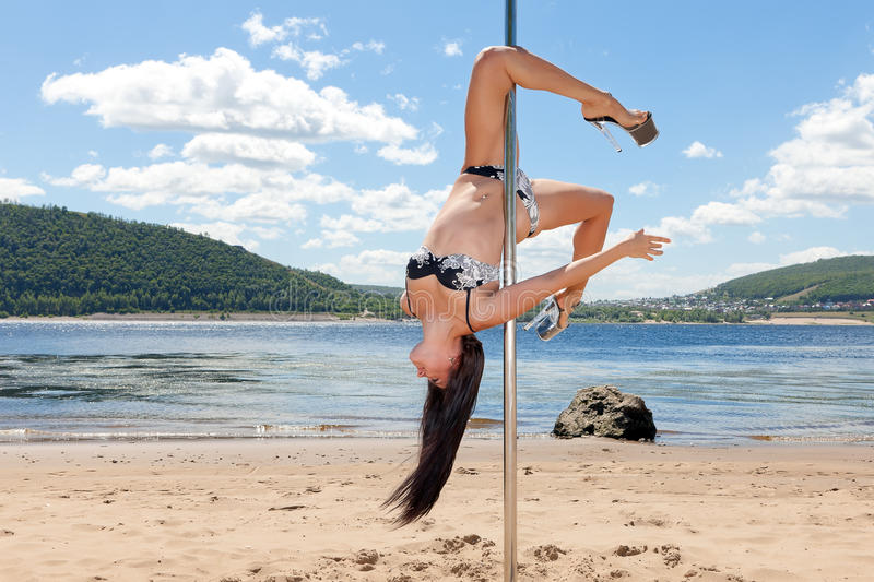 Dancer on pole upside down background of summer beach and blue sky stock image