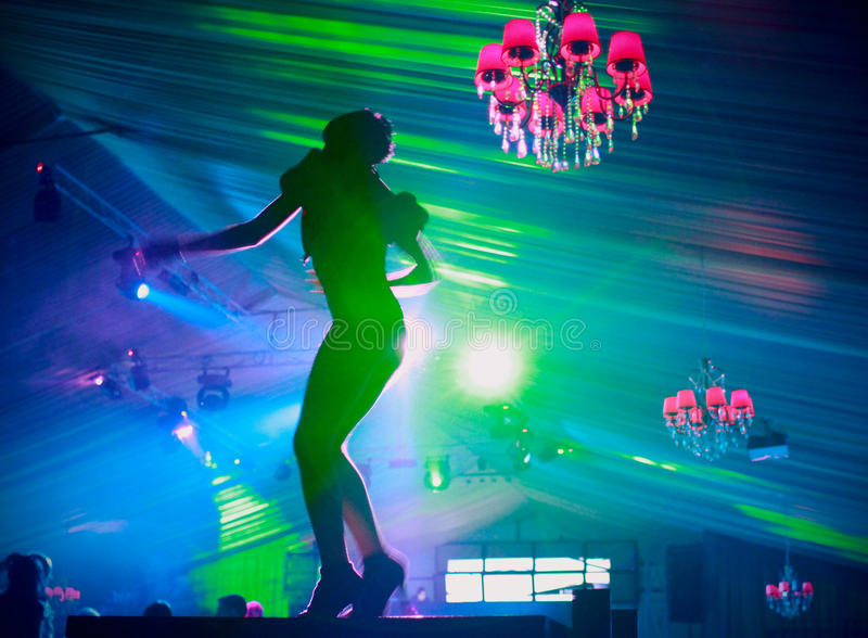 Dancer silhouette in the nightclub. Silhouette of young female dancer who is entertaining the partying audience in a nightclub royalty free stock photography