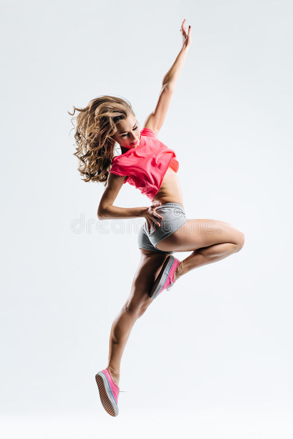 The dancer. Young beautiful dancer jumping on a studio background stock photos