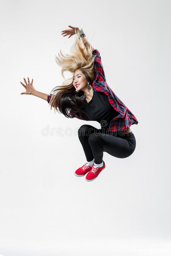 The dancer. Young beautiful dancer jumping on a studio background stock images