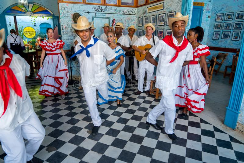 Dancers and musicians perform cuban folk dance. Dancers in costumes and musicians perform traditional cuban folk dance in cafe in Trinidad. Cuba, spring 2018 royalty free stock photography