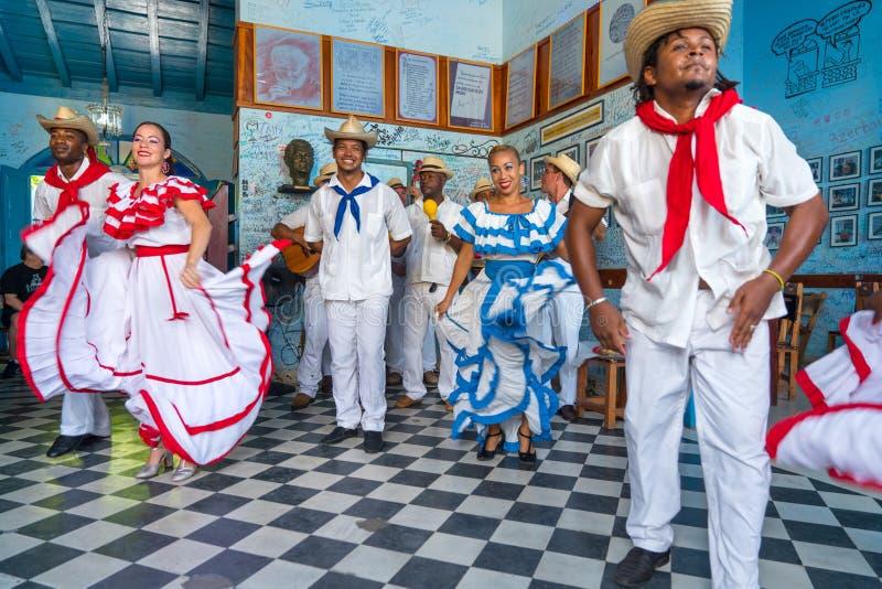 Dancers and musicians perform cuban folk dance. Dancers in costumes and musicians perform traditional cuban folk dance in cafe in Trinidad. Cuba, spring 2018 stock photography