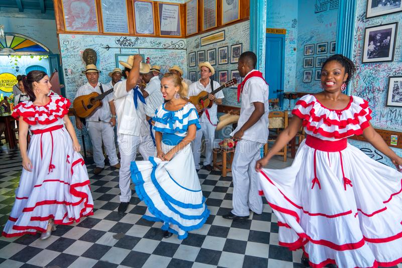 Dancers and musicians perform cuban folk dance. Dancers in costumes and musicians perform traditional cuban folk dance in cafe in Trinidad. Cuba, spring 2018 royalty free stock photo