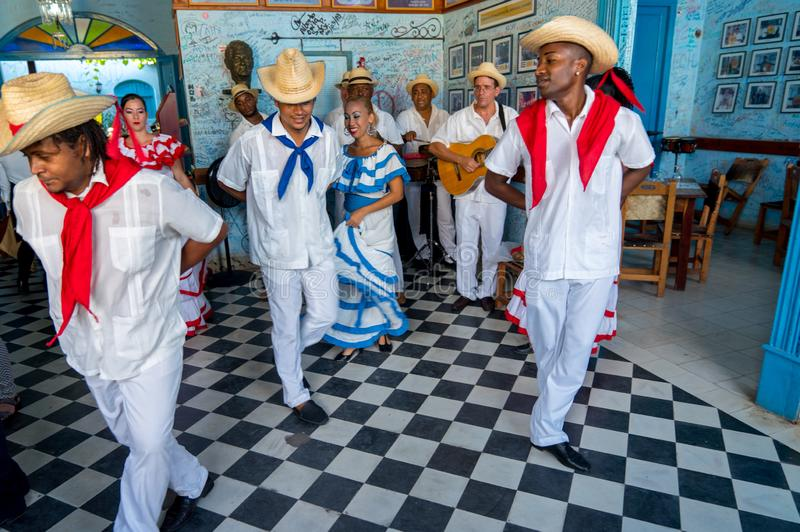 Dancers and musicians perform cuban folk dance. Dancers in costumes and musicians perform traditional cuban folk dance in cafe in Trinidad. Cuba, spring 2018 stock photo