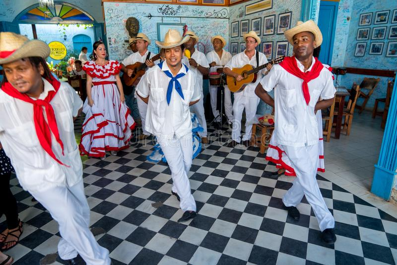 Dancers and musicians perform cuban folk dance. Dancers in costumes and musicians perform traditional cuban folk dance in cafe in Trinidad. Cuba, spring 2018 royalty free stock images