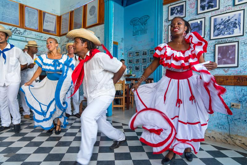 Dancers and musicians perform cuban folk dance. Dancers in costumes and musicians perform traditional cuban folk dance in cafe in Trinidad. Cuba, spring 2018 stock photography
