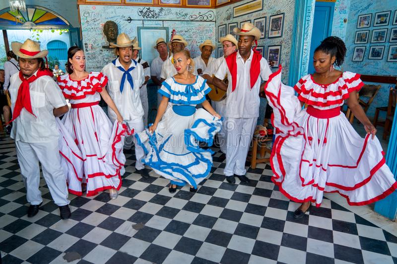 Dancers and musicians perform cuban folk dance. Dancers in costumes and musicians perform traditional cuban folk dance in cafe in Trinidad. Cuba, spring 2018 royalty free stock image