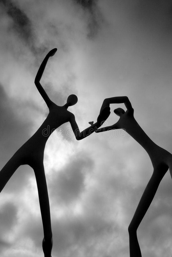 Dancers Silhouetted Against Cloudy Sky. Statue depicting two dancers is silhouetted against cloudy sky royalty free stock photos