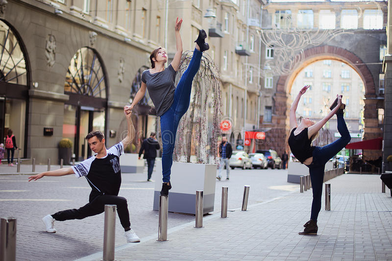 Dancers on the street. Two girls and boy jumping and dancing on city streets stock photos