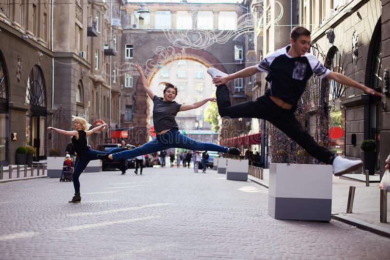 Dancers on the street. Two girls and boy jumping and dancing on city streets stock photography