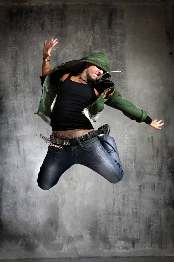 Dancing. Cool looking dancer jumping behind grunge grey wall stock photo