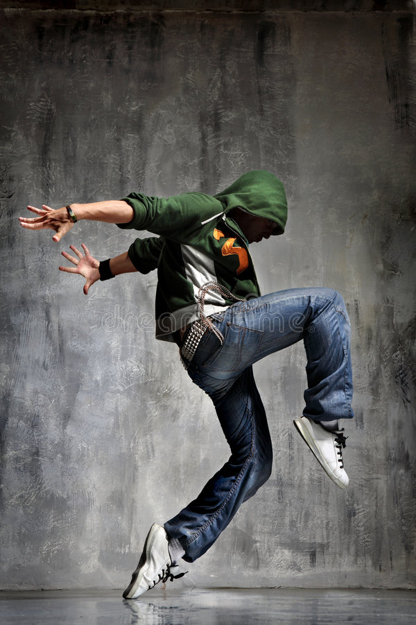 Dancing. Cool looking dancer jumping on grey grunge wall background royalty free stock photos