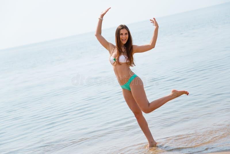 Dancing allegro della ragazza sulla spiaggia fotografia stock