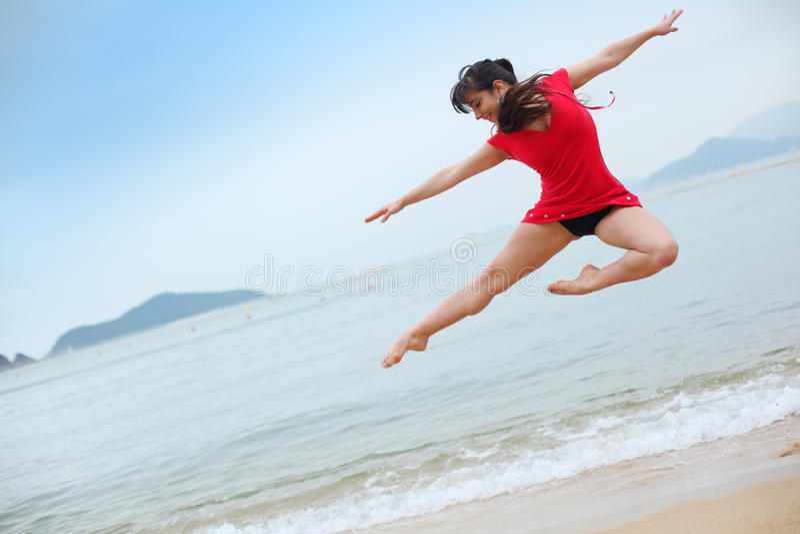 Dancing on beach. Beautiful young woman dancing on beach stock photography