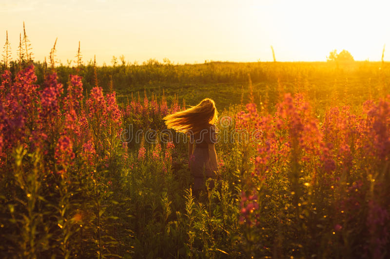 Dancing beautiful girl on field, sun backlight, sunrise. Orange colors, hands near the neck stock images