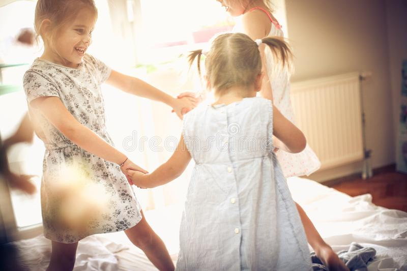 Dancing on bed. Three little girls dancing in bed. Space for copy stock photo