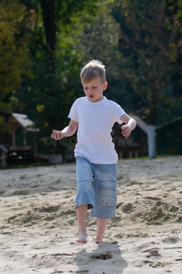 Dancing boy on the beach. In white t-shirt royalty free stock photography