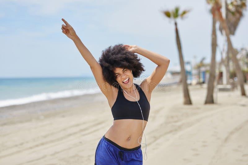 Dancing d'ascolto di musica della donna afroamericana sul divertiresi della spiaggia fotografie stock