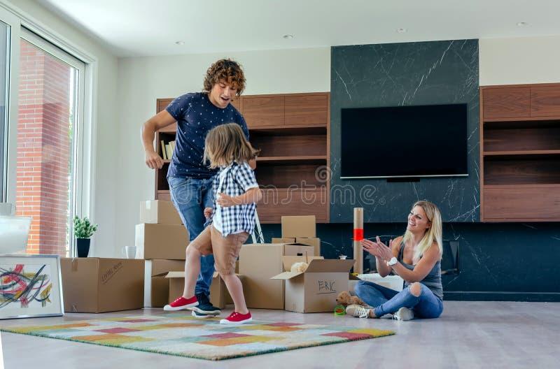 Dancing del figlio e del padre mentre la madre li esamina immagini stock libere da diritti