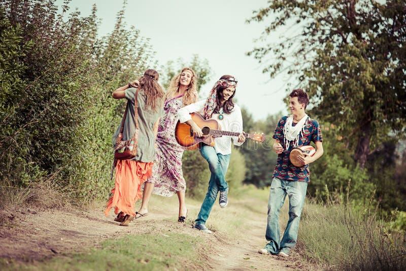 Dancing del gruppo del Hippie nella campagna fotografie stock