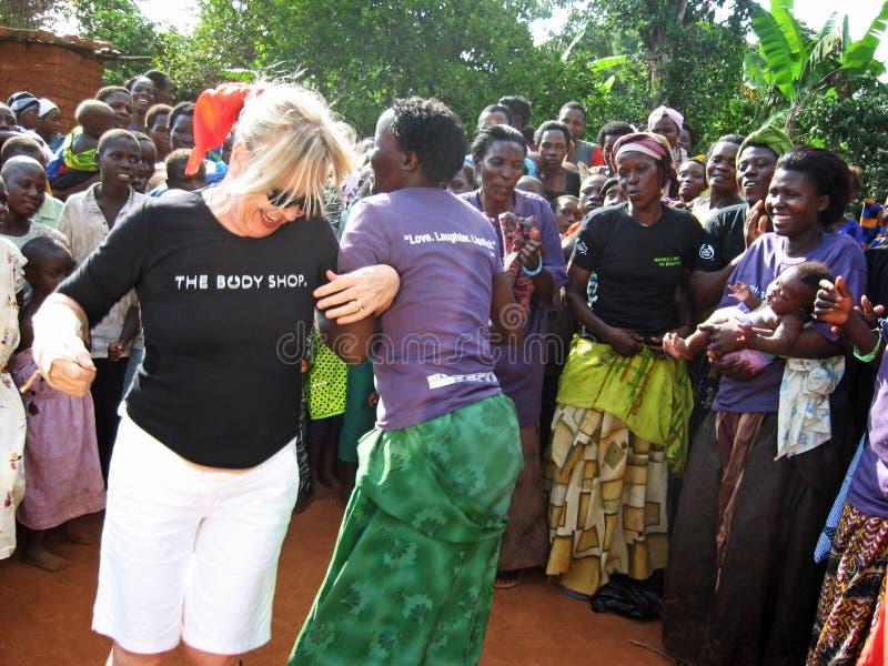 Dancing del lavoratore umanitario della donna bianca e dell'Africano per la gioia davanti ai paesani Uganda Africa fotografie stock