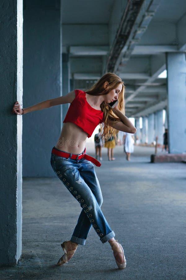 Dancing della ballerina con un telefono cellulare Prestazione della via fotografie stock libere da diritti