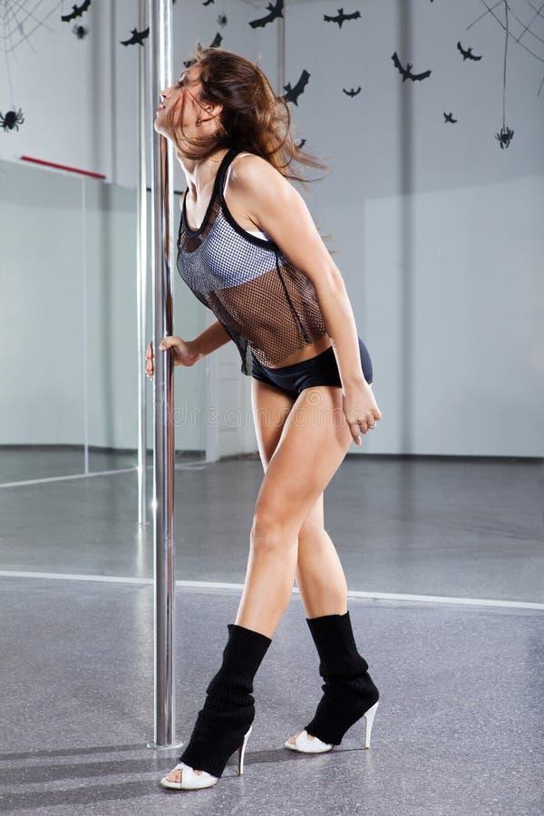 Dancing della giovane donna con il palo fotografia stock