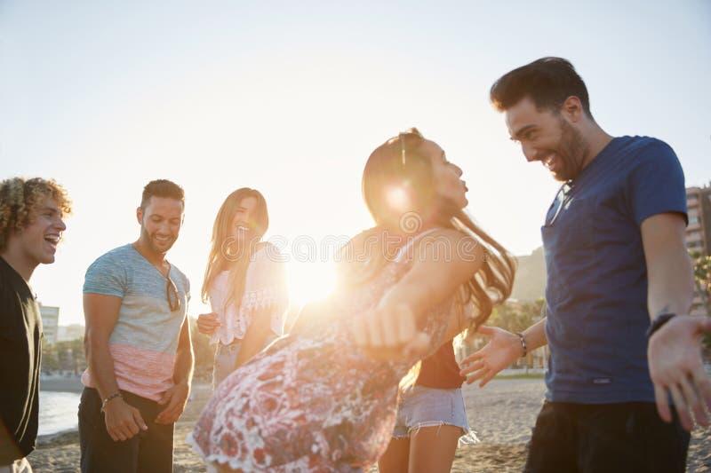 Dancing delle coppie sulla spiaggia che fa festa con gli amici immagini stock libere da diritti