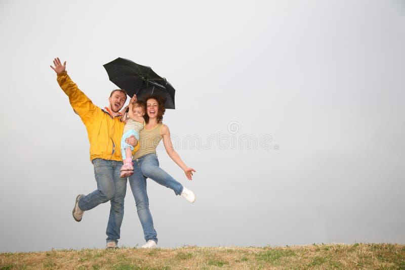 Dancing family under umbrella stock image
