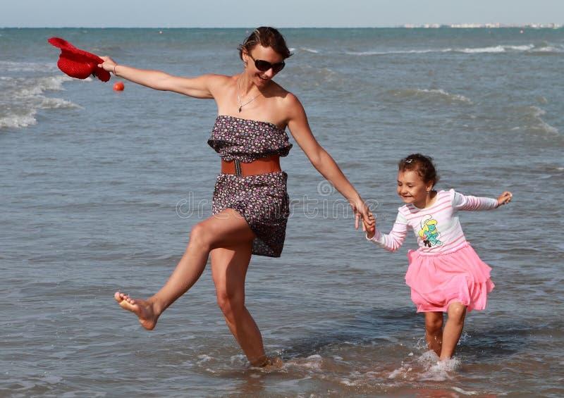 Dancing felice della famiglia in mare immagini stock