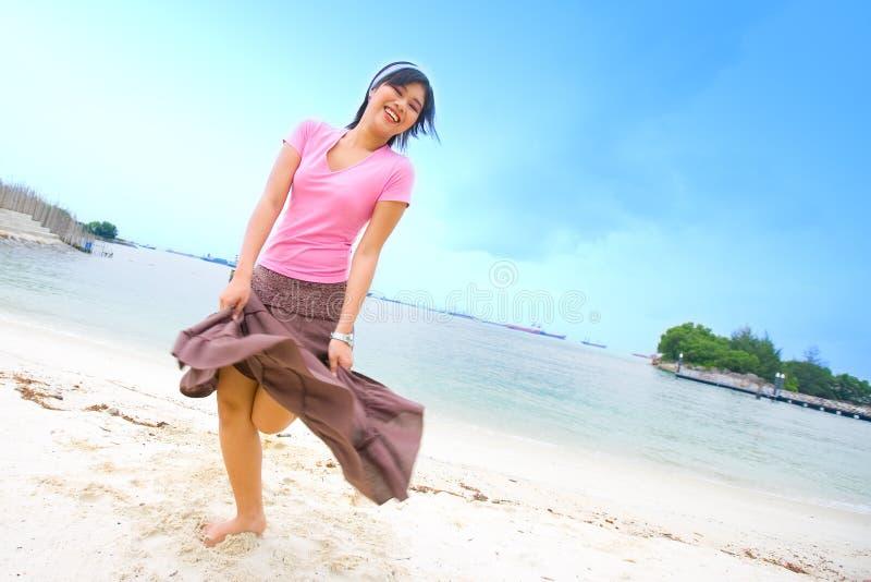 Dancing femminile asiatico felice sulla spiaggia fotografie stock