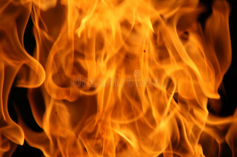 The dancing fire. Intrigued with the dancing flames of the fire in the fire pit, beautiful colors, hot & contained royalty free stock photos