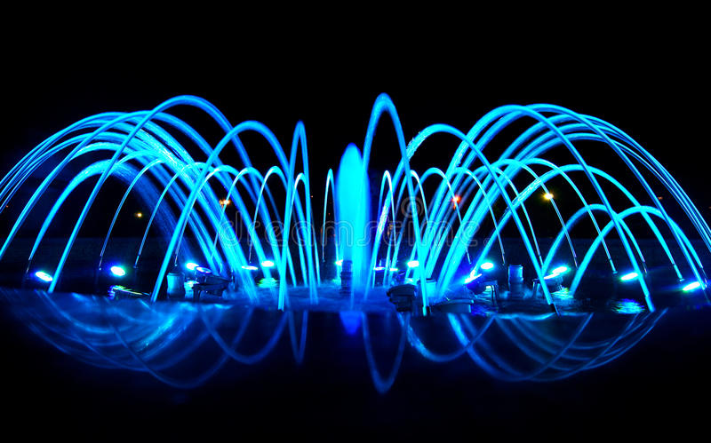 Dancing fountain at night, blue color stock photo