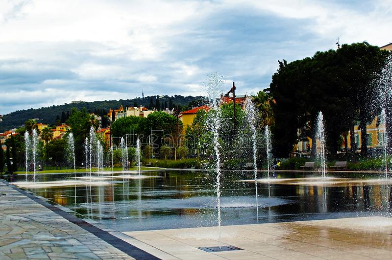 Dancing fountains square in Nice, France with vibrant houses, trees and bright blue sky. Dancing fountains square with vibrant houses, trees and bright blue sky royalty free stock images