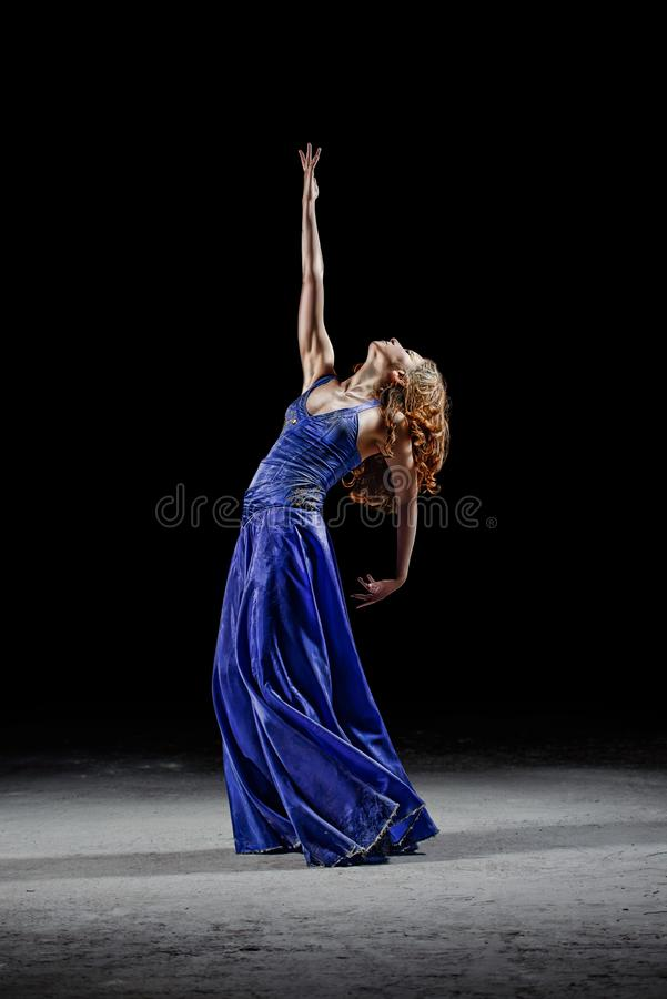 Dancing girl in the darkness. Raises her hand up. stock photo
