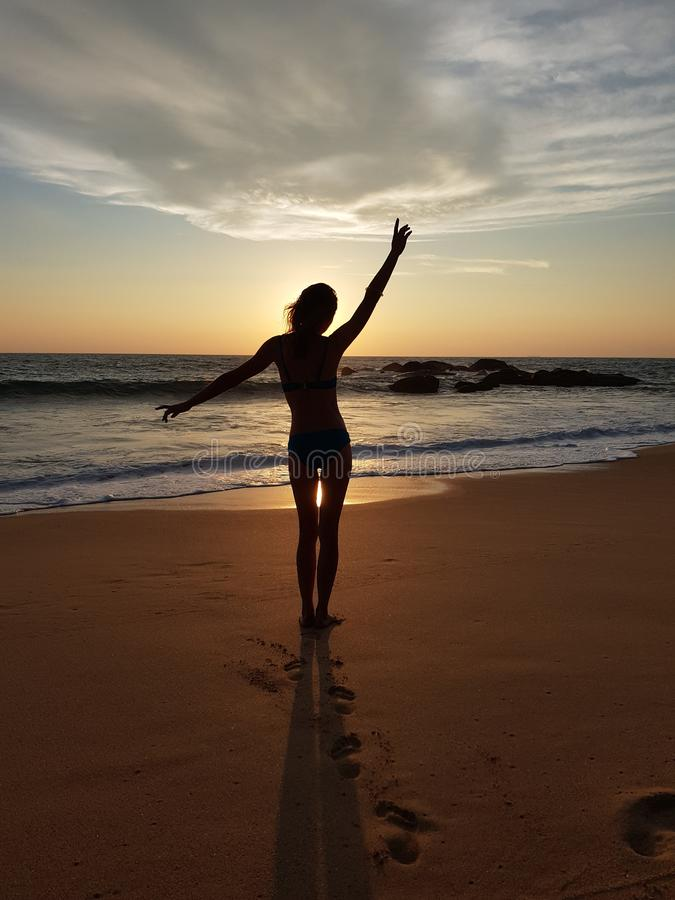 Dancing girl at sunset on the Indian Ocean royalty free stock photo