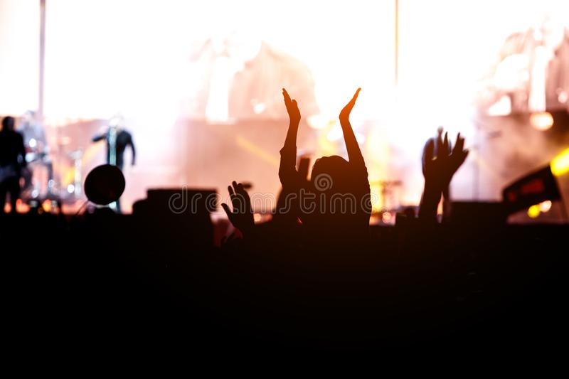 Dancing girl on shoulders in the crowd at a music festival stock photo