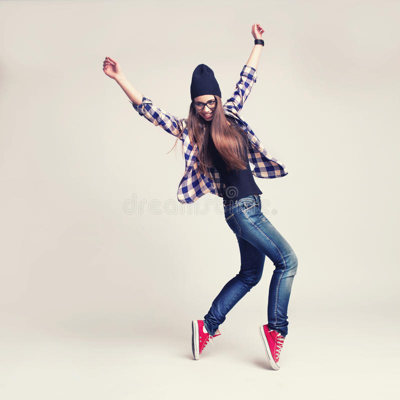 Dancing hipster girl in glasses and black beanie stock image