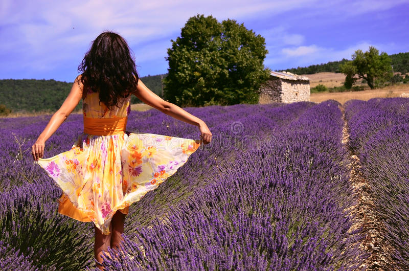 Woman wearing a floating dress in a lavender field stock photo