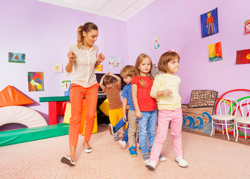 Dancing lesson with kids repeat after teacher. Dancing lesson in kindergarten class with boys and girls repeating after teacher royalty free stock photo