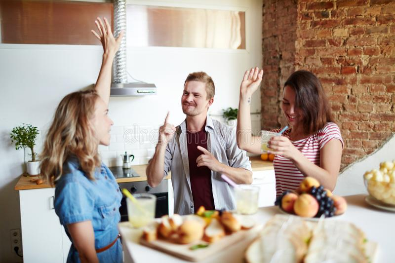 Dancing after lunch. Young dancing friends with drinks having home party in the kitchen royalty free stock image